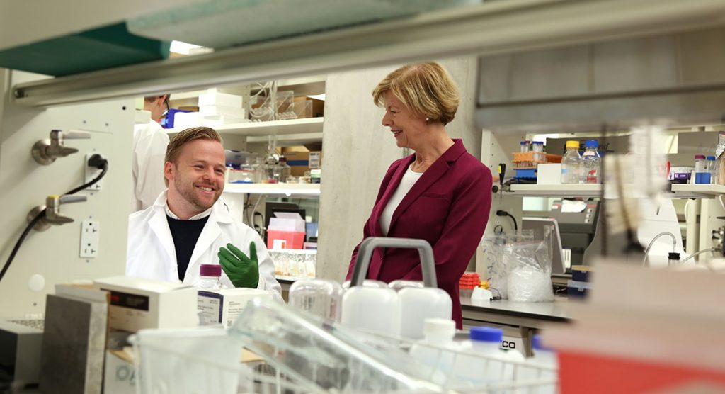 Mateusz Manicki, a postdoctoral fellow in the Pagliarini Lab at Morgridge, discusses his research with Tammy Baldwin during her visit.
